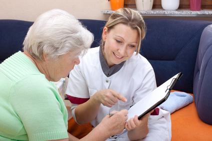Seniorin und Pflegerin sitzen beieinander