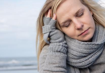 blonde Frau fässt sich an den Kopf aufgrund von Kopfschmerzen