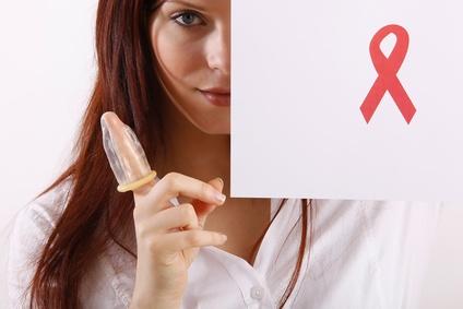 Schöne Frau mit Kondom auf dem Finger achtet auf Verhütung