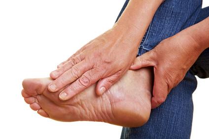 Hände berühren die Fußsohle