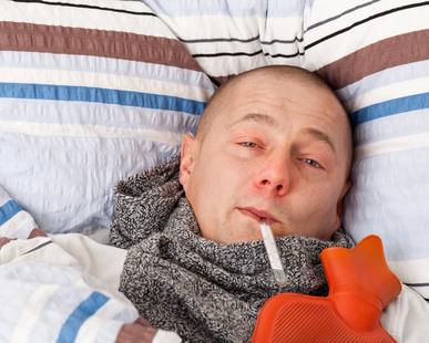 Kranker Mann mit Wärmeflasche und Fieberthermometer