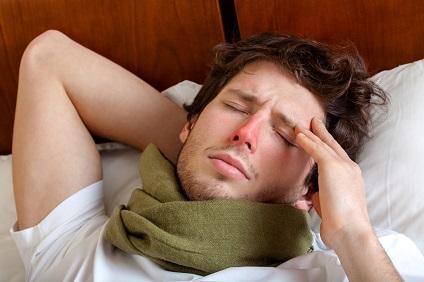 Mann liegt mit Grippe im Bett