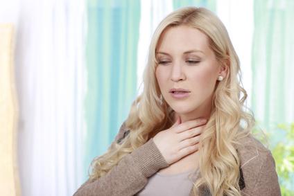 Hübsche Frau mit Schluckbeschwerden und Halsschmerzen
